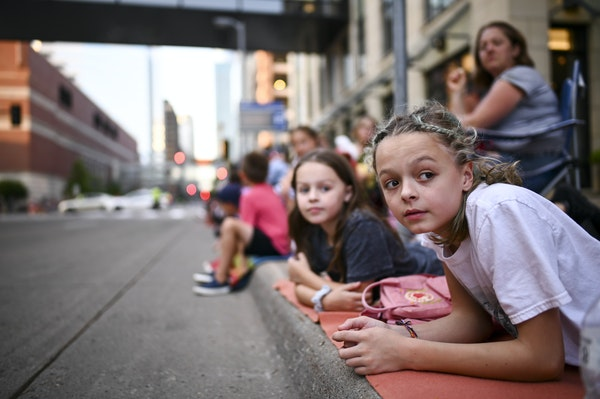 Axel Romann, right, 12, and his sister Harley, 9, from Jordan, waited for the start of the Aquatennial Torchlight Parade to begin along 2nd Avenue in