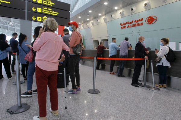 Travelers queue at the Houari Boumediene airport for a flight bound to Paris, Tuesday, June 1, 2021 in Algiers. Algeria has partially reopened its air