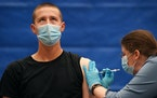 Hayden Ring, 21, looked up as he got his second dose of the Pfizer COVID-19 vaccine during a free COVID-19 vaccination event at Hamline University in
