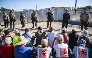 Law enforcement officers formed a line between protesters and an Enbridge pump station Monday.