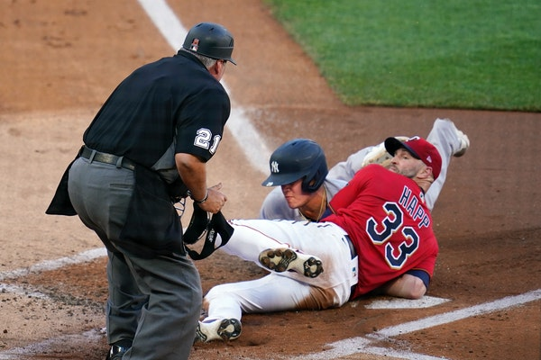 Twins pitcher J.A. Happ looks for the call by umpire Hunter Wendelstedt after tagging Yankees' Gio Urshela at the plate during the first inning