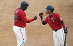 Minnesota Twins' Miguel Sano (22) and Jorge Polanco bump fists after Sano scored on an Andrelton Simmons double off New York Yankees pitcher Michael