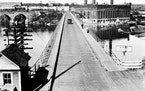 A view of the 10th Avenue Bridge looking east in the 1920s. The Twin City Rapid Transit Steam Power Plant is in the right background, the Stone Arch B