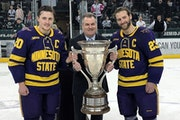 WCHA Commissioner Bill Robertson presented the MacNaughton Cup to Minnesota State Mankato's Marc Michaelis, left, and Nick Rivera in 2019.