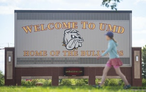 A woman walked past the University of Minnesota Duluth football stadium last summer. The pandemic caused enrollment decline at UMD and other area coll