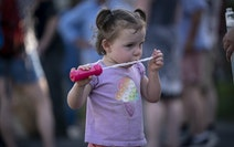 Lenora Cordes, 2, played with a bubble wand while mom Melissa Cordes chatted with neighbors during a food truck event in Arden Hills on Friday.