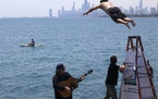 """Dan O'Conor, the """"Great Lake Jumper,"""" makes his 365th leap into Lake Michigan, Saturday, June 12, 2021, in Chicago's Montrose Point. (AP Photo"""