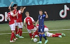 Denmark's players go to their teammate Christian Eriksen after he collapsed during a Euro 2020 match in Copenhagen, Denmark, Saturday, June 12, 2021