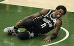 Nets guard Kyrie Irving held his leg after being injured during the first half of Game 4 of the Eastern Conference semifinals against the Bucks on Sun