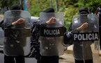 Riot police stand guard outside the house of Cristiana Chamorro, former director of the Violeta Barrios de Chamorro Foundation and pre-presidential ca