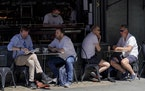 People sit at outdoor tables at a restaurant in Soho, in London, Monday, June 14, 2021. British Prime Minister Boris Johnson is expected to confirm Mo