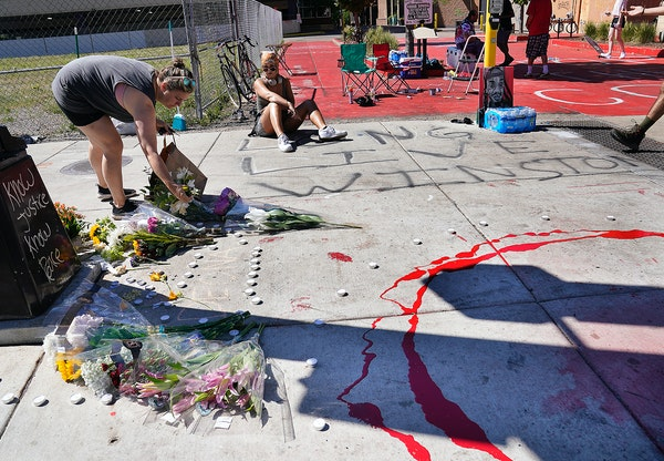 Steph Opitz of Minneapolis left flowers at a growing memorial to a woman killed at the intersection in Uptown late Sunday and seen Monday in Minneapol