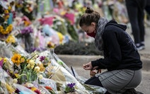 A woman burns incense at a memorial for shooting victims at a King Soopers Grocery store on March 26, 2021, in Boulder, Colorado.