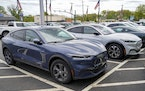 A pair of 2021 Ford Mustang Mach E are displayed for sale at a Ford dealer on Thursday, May 6, 2021, in Wexford, Pa. Retail sales fell in May, dragged