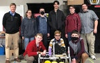 The Eagle Ridge Academy robotics team poses with the robot used in this year's competition season.