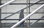 A man, donning a surgical mask, walked through the skyway attached to HCMC.