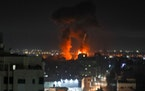 Explosions light-up the night sky above buildings in Gaza City as Israeli forces shell the Palestinian enclave, early on Wednesday.