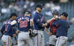 Minnesota Twins starting pitcher J.A. Happ, center, meets at the mound with pitching coach Wes Johnson, right, shortstop Jorge Polanco (11), third bas