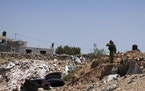 An Israeli soldier stands near a car said to be used in an attack near Hizmeh Junction in the West Bank, Wednesday, June 16, 2021. The Israeli militar