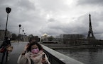 FILE - In this Thursday, March 18, 2021 file photo, women cross a bridge as the Eiffel Tower is seen background in Paris. The European Union is recomm