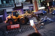 A loader cleared out barricades put up by protestors on W. Lake Street in Uptown on Tuesday in Minneapolis.