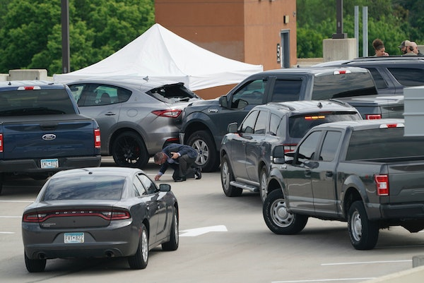 An investigator goes through the scene a shooting on the top of a parking ramp in Minneapolis, on June 3, 2021, when Winston Smith was shot and killed
