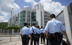Police officers stand guard outside Apple Daily headquarters in Hong Kong, Thursday, June 17, 2021