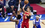 Atlanta Hawks' Trae Young goes up for a shot against Philadelphia 76ers' Joel Embiid (21), Matisse Thybulle (22) and Seth Curry (31) during the se