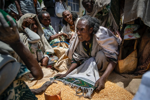 An Ethiopian woman argues with others over the allocation of yellow split peas after it was distributed by the Relief Society of Tigray in the town of