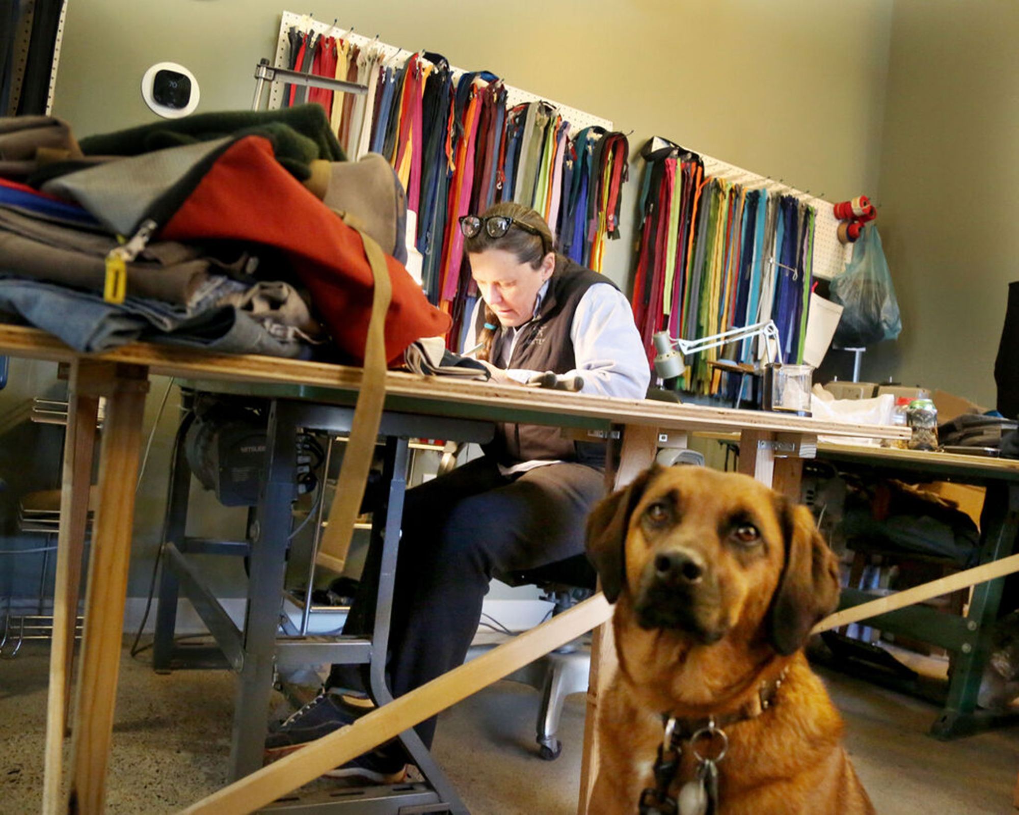 Repair Lair owner Nancy Ford works on replacing a zipper on a pair of bike pants at her Minneapolis consignment shop specializing in outdoor clothing, accessories and repair.