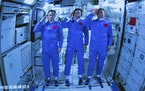 In this photo released by Xinhua News Agency, Chinese astronauts salute after successfully entering the Tianhe space station module as they are displa