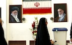 A woman casts her vote during the presidential election at a polling station inside the Iranian consulate in Karbala, Iraq, Friday, June 18, 2021. Ira