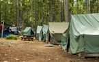 A typical campsite at a Boy Scout Camp includes tents, a table, dirt, and dirty clothes drying on a rope.