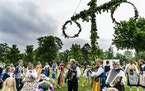 Both adults and children dance around the maypole to celebrate midsummer.