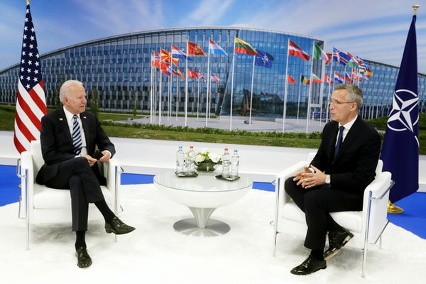 NATO Secretary General Jens Stoltenberg speaks with U.S. President Joe Biden during a bilateral meeting on the sidelines of a NATO summit at NATO head