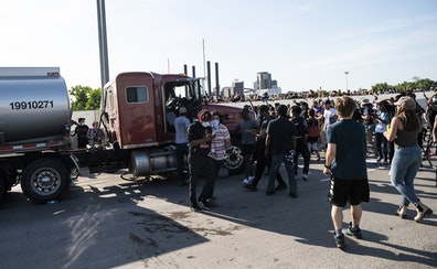 People react after a tanker truck drove into a crowd peacefully protesting the death of George Floyd on the I-35W bridge over the Mississippi River on