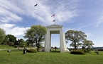 In this May 17, 2020, file photo, a bird flies from the U.S. into Canada over the Peace Arch in Peace Arch Historical State Park in Blaine, Wash.