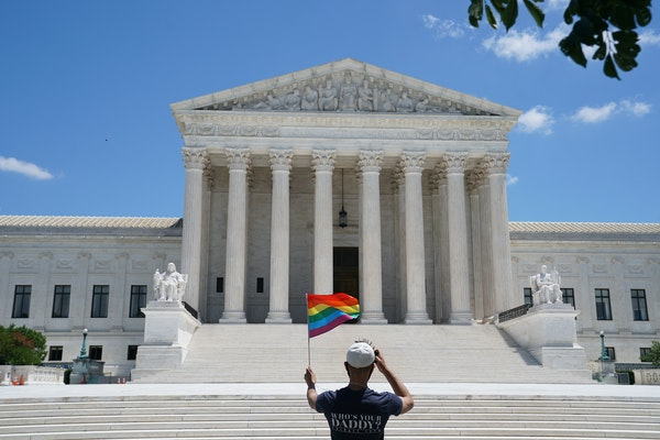 A person waves a rainbow flag in front of the Supreme Court in Washington, on June 15, 2020.