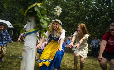 Sisters Natalie Redinger, center, and Heather Dewitt, right, participate in a traditional Swedish circle dance Thursday at the American Swedish Instit