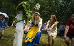 Sisters Natalie Redinger, center, and Heather Dewitt, center right, participate in a traditional Swedish circle dance around a maypole in honor of an