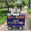 Willa reveals fortunes on the other side of colorful art she hangs above her lemonade stand.