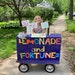 Photos by IMANI CRUZEN@Caption:Willa reveals fortunes on the other side of colorful art she hangs above her lemonade stand.