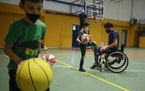 Adolfo Damian Berdun, of Argentina, a professional player and captain of the Argentine basketball Paralympic team, teaches children basketball at a pr
