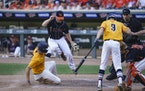Grand Rapids High School's pitcher Andrew Sundberg leapt up as Mahtomedi High School's Tony Neubeck slid safely into home plate in the sixth innin