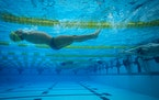 Swimmer Abbas Karimi, who was born without arms and is a refugee from Afghanistan, warmed up in the pool before the second day of preliminaries during