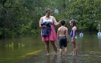 Jessie Kingsmill stands in her driveway with her children Marina, 8, right, and Raylan, 8, as water recedes after Tropical Storm Claudette passed thro