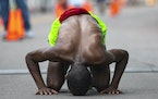 A runner touched his forehead to the ground after crossing the finish line in Grandma's Marathon on Saturday morning with a time of 2:29:04.