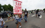 A woman carries a sign during a parade to mark Juneteenth on Saturday, June 19, 2021, in Denver.