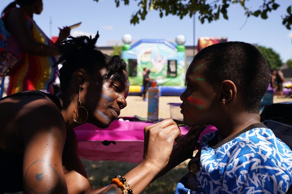 Kiara James painted the face of Sincerr Ancrum, 4, during a gathering to celebrate Juneteenth Saturday at Sanctuary Covenant Church in Minneapolis.