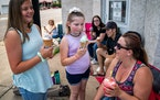 Brittany Bastian laughed as her daughters Keilie, 11, and Jaselynn, 8 licked their rapidly melting ice cream cones while they waited for the parade to